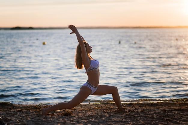 Кавказская женщина подходит со спортивным телом, позирует на пляже во время заката. похудание к лету, мотивация. Premium Фотографии