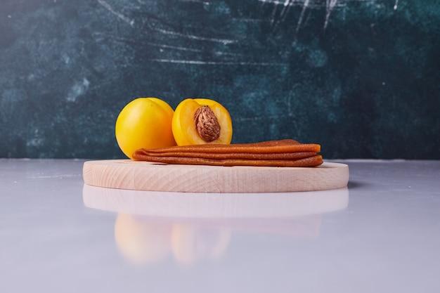 青の背景に白のプレートに黄色の桃と白人のフルーツラヴァッシュ。高品質の写真 無料写真
