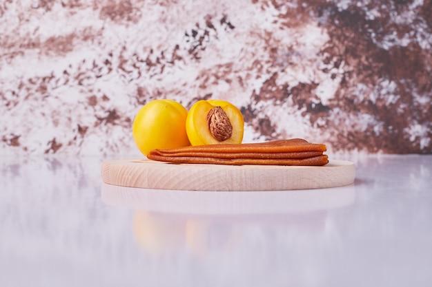 Кавказский фруктовый лаваш с желтыми персиками в белой тарелке на мраморе. Бесплатные Фотографии