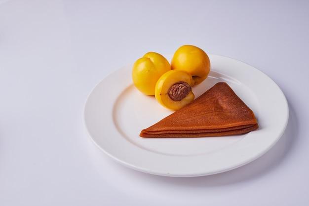 Кавказский фруктовый лаваш с желтыми персиками в белой тарелке. Бесплатные Фотографии