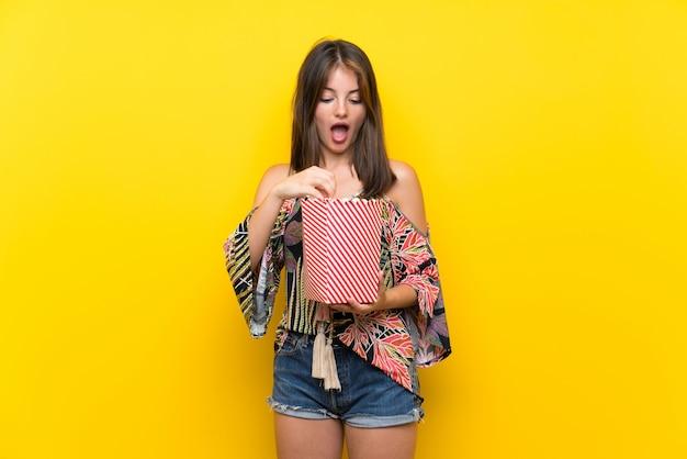 Caucasian girl in colorful dress eating popcorns Premium Photo