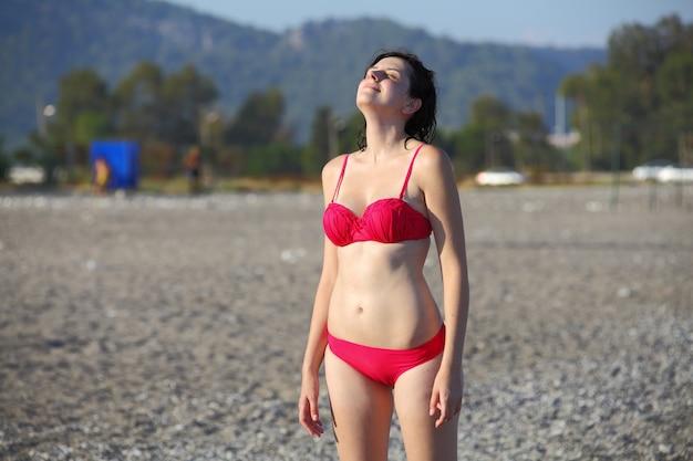분홍색 수영복에 백인 여자, 터키의 조약돌 해변에 서있는 태양, 그리고 그의 눈을 감고, 리조트 타운. 프리미엄 사진