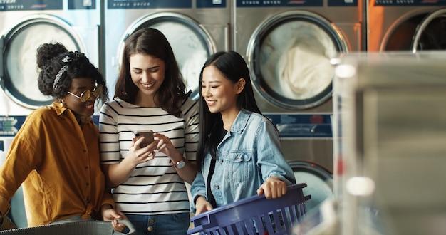白人の女の子は、洗濯機で作業し、服を掃除しながら、混血の女性の友人にスマートフォンで写真を見せています。ランドリーサービスで電話でビデオを見て多民族の女性。 Premium写真