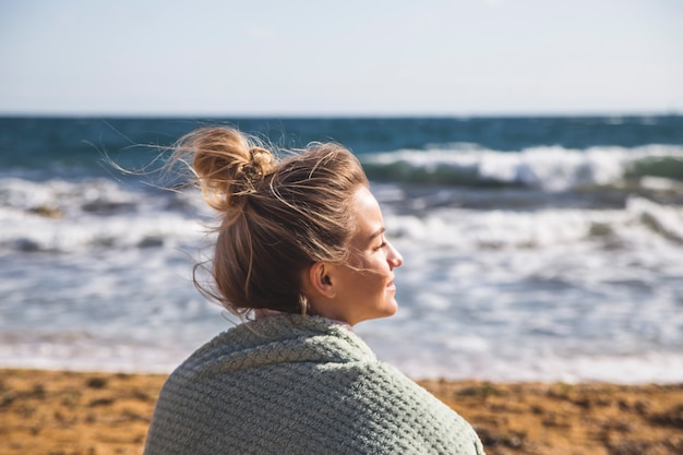 A caucasian girl sits on the sand by the sea, closing her eyes and enjoying a trip to nature. Premium Photo