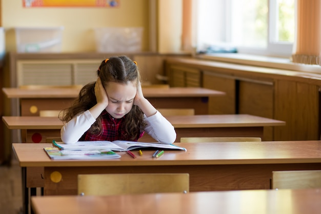 Caucasian girl sitting at desk in class room and hard to learn lessons. preparation for exams, tests Premium Photo