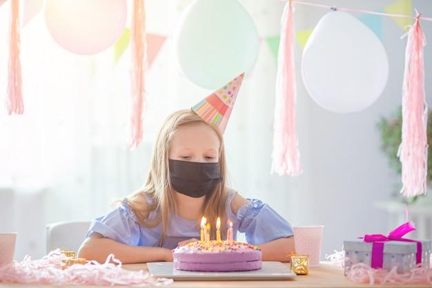 白人の女の子は彼女の誕生日にマスクを着用します。風船でお祭りのカラフルな背景。誕生日パーティーと願いのコンセプトです。 Premium写真