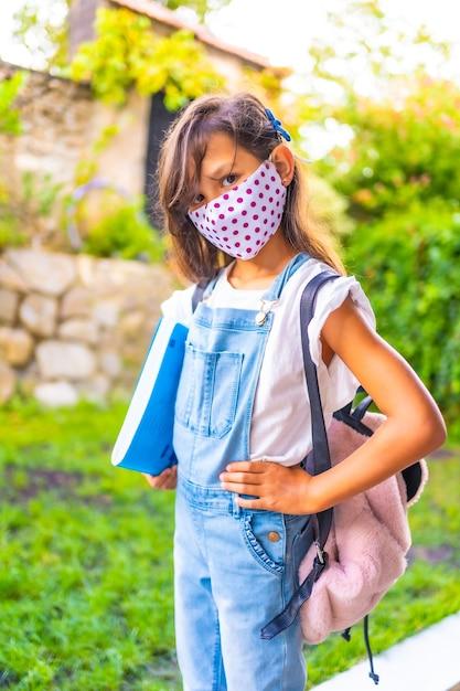 フェイスマスクが学校に戻る準備ができている白人の女の子。新しい正常性、社会的距離、コロナウイルスのパンデミック、covid-19。ジャケット、バックパック、手元のメモ用の青いブロック Premium写真