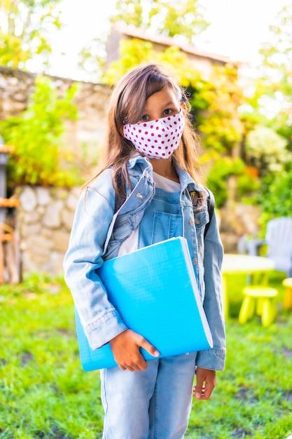 フェイスマスクが学校に戻る準備ができている白人の女の子。新しい正常性、社会的距離、コロナウイルスのパンデミック、covid-19。ジャケット、バックパック、ピンクのドットのマスク、手に青いブロック Premium写真
