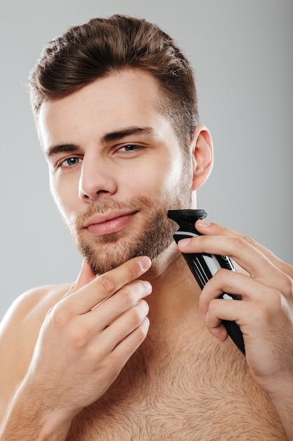 Caucasian guy 30s being undressed at home touching his chin and shaving face with trimmer over grey wall Free Photo