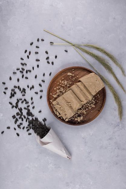 木製の大皿にヒマワリの種から作られた白人のハルヴァ 無料写真