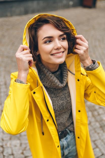 フードを着て、都市公園を歩きながら天気を楽しんで黄色のレインコートで白人の楽しい女性 無料写真