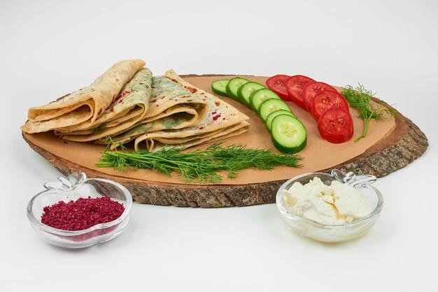 白の木製ボードにスパイスと野菜を添えた白人のクタブ。 無料写真