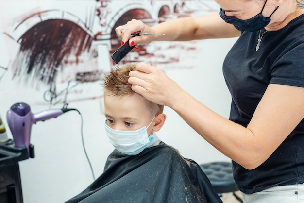 Caucasian little boy getting hair cut at the barbershop wearing protective mask Premium Photo