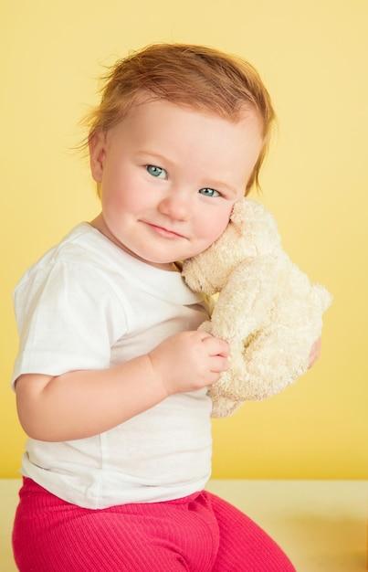 白人の少女、黄色のスタジオの背景に孤立した子供たち。キュートで愛らしい子供の肖像画、遊んでいる赤ちゃんと笑顔。 無料写真