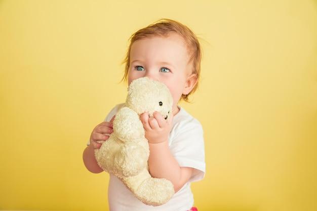 백인 어린 소녀, 노란색 스튜디오 배경에 고립 된 어린이. 귀 엽 고 사랑스러운 아이, 아기 테 디 베어와 함께 연주의 초상화. 무료 사진