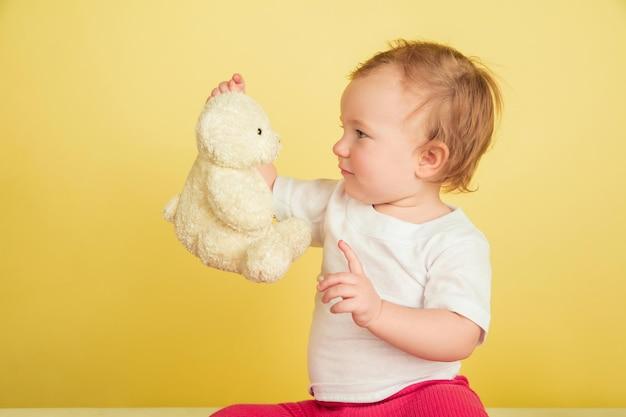 白人の少女、黄色のスタジオの背景に孤立した子供たち。キュートで愛らしい子供の肖像画、テディベアと遊ぶ赤ちゃん。 無料写真