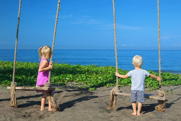 Caucasian little kids - girl and boy have fun together on rope swing at black sand beach on summer family vacation. Premium Photo