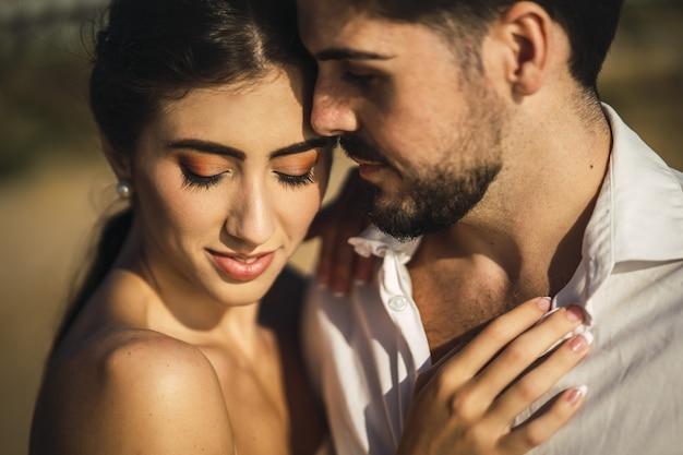Кавказская влюбленная пара в белой одежде и обниматься на пляже во время свадебной фотосессии Бесплатные Фотографии