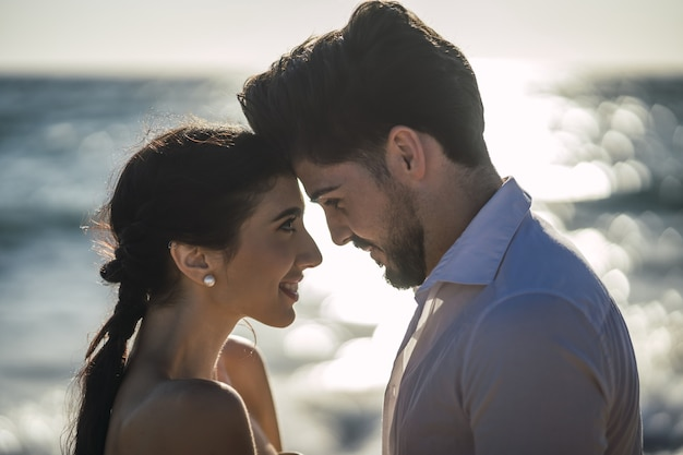 Caucasian loving couple wearing white clothes and hugging in the beach during a wedding photoshoot Free Photo