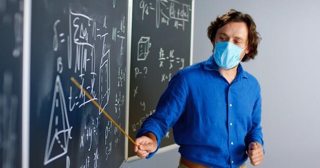 Кавказский учитель-мужчина в медицинской маске стоит за доской в классе и рассказывает классу законы физики или геометрии. концепция пандемии. школа во время коронавируса. лекция по учебной математике. Premium Фотографии