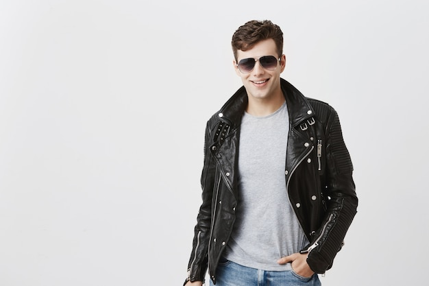 Caucasian male with appeal look, smiling broadly with white even teeth, posing indoors. stylish handsome attractive man with trendy haircut dressed in black leather jacket,with sunglasses on. Free Photo