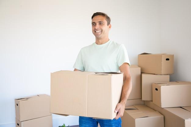彼の新しい家やアパートでカートンボックスを運ぶ白人男性 無料写真