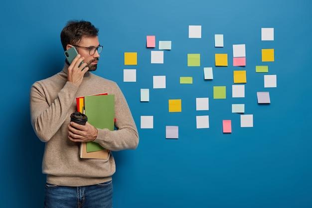 L'uomo caucasico ha un approccio creativo all'organizzazione del lavoro, lascia adesivi colorati sul muro, discute l'orario di lavoro con il partner tramite smartphone Foto Gratuite