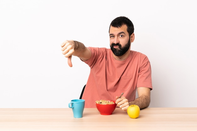 Caucasian man having breakfast in a table showing thumb down with negative expression Premium Photo