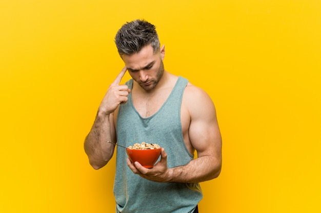 Caucasian man holding a cereal bowl pointing his temple with finger, thinking, focused on a task. Premium Photo