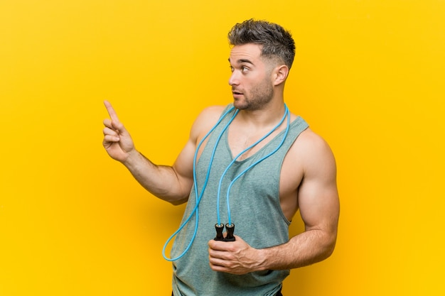 Caucasian man holding a jump rope smiling cheerfully pointing with forefinger away. Premium Photo