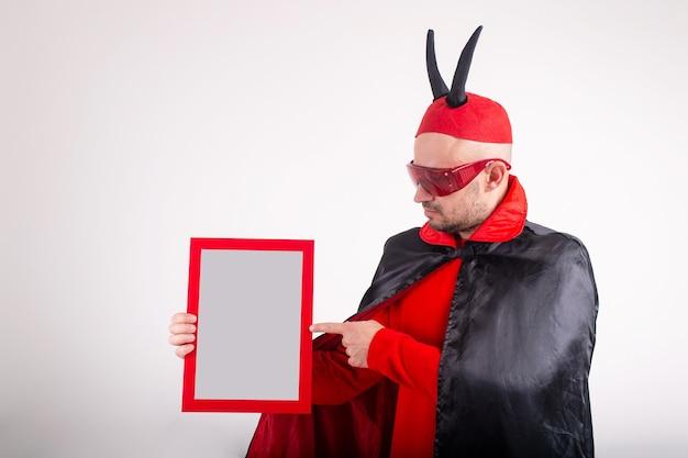 흰색 스튜디오 배경 위에 빈 명판을 보여주는 할로윈 의상 백인 남자. 프리미엄 사진