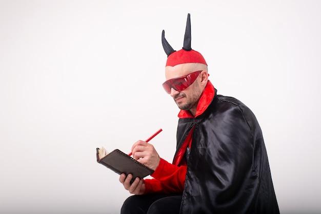 빨간 선글라스와 흰색 스튜디오 배경 위에 펜 및 노트북 할로윈 의상 백인 남자. 프리미엄 사진