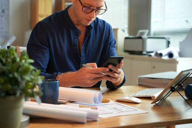 Caucasian man sitting at desk with rolled-up papers and plans and using smartphone Free Photo