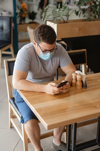 Caucasian man sitting in restaurant and using phone in medical face mask. new normal concept Premium Photo