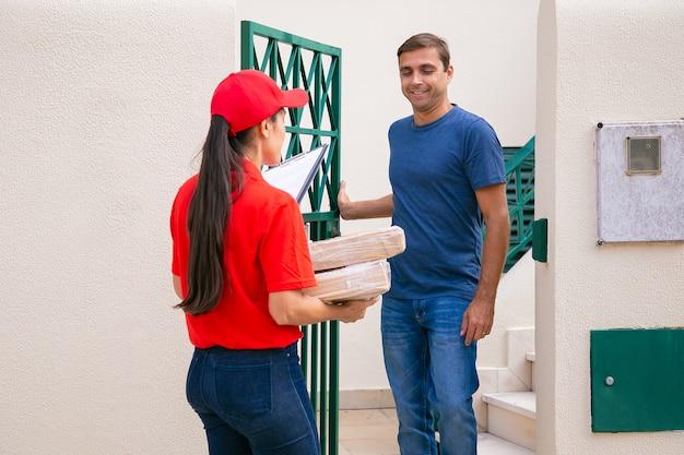 屋外に立って配達人に会う白人男性。赤い帽子とシャツを着たプロの宅配便業者が、小包や箱を徒歩で顧客に配達します。速達サービスとポストコンセプト 無料写真