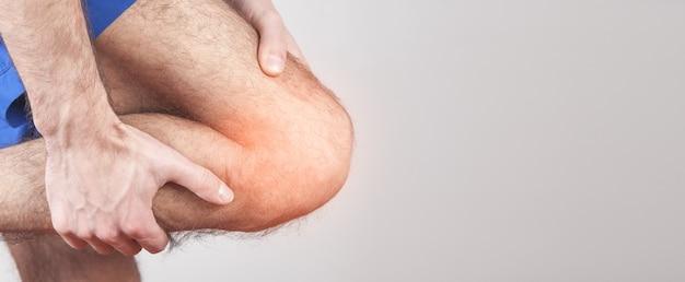Кавказский мужчина страдает от боли в колене. Premium Фотографии