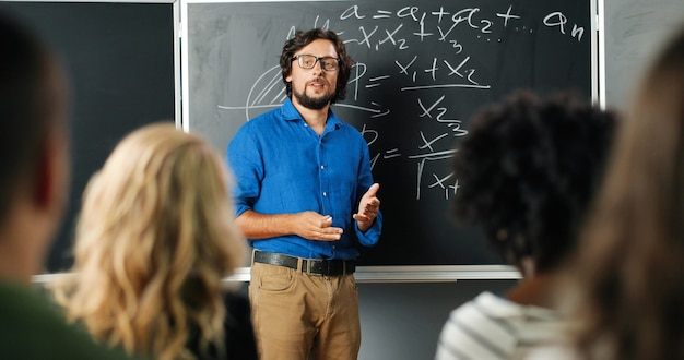 Caucasian man teacher at school at blackboard talking with pupils or students and asking question. math class concept. male lecturer in glasses explaining mathematics laws to kids. educational concept Premium Photo