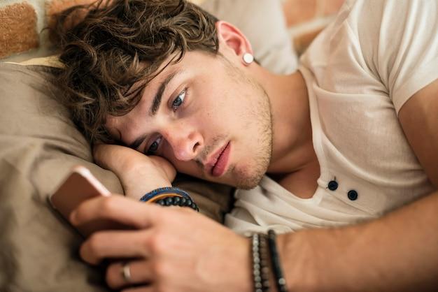 Caucasian man using mobile phone in bed Premium Photo