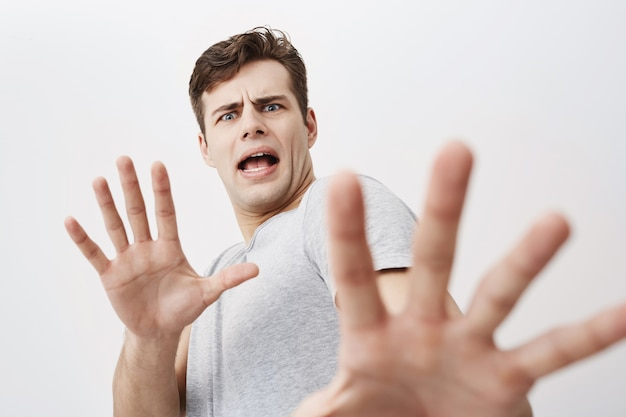 Caucasian man with scared expression on his face making frightened gesture with his palms as if trying to defend himself. fearful european young male asking to stop, gesturing with his hands Free Photo