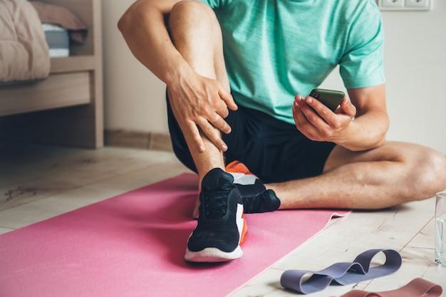 電話を見ながら朝の運動をした後、自宅で働いている白人男性が休んでいます Premium写真