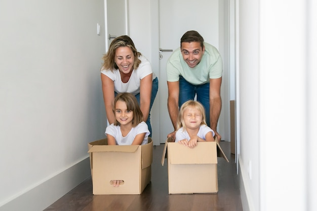 Caucasian mom and dad pushing cardboard boxes with kids inside Free Photo