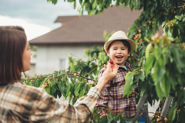 帽子をかぶった白人の母親と息子が笑顔で庭でさくらんぼを食べています Premium写真