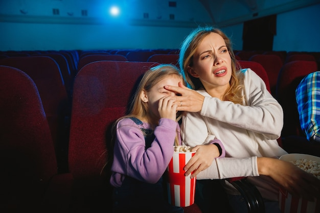 Caucasian mother and daughter watching a film at a movie theater, house or cinema. Free Photo