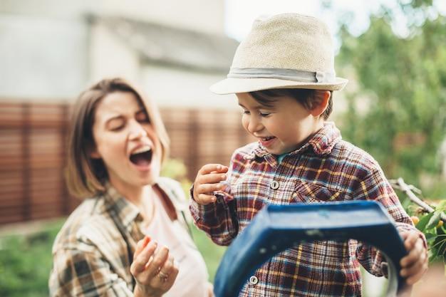 茶色の髪の白人の母親と帽子をかぶった幼い息子がさくらんぼを食べて笑っている Premium写真