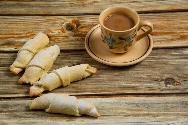 一杯のコーヒーと木製のテーブルの上の白人菓子ムタキ 無料写真