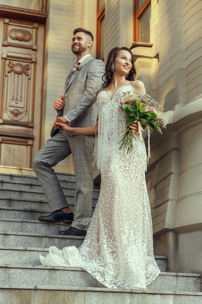 Caucasian romantic young couple celebrating their marriage in city. tender bride and groom on modern city's street. family, relationship, love concept Free Photo