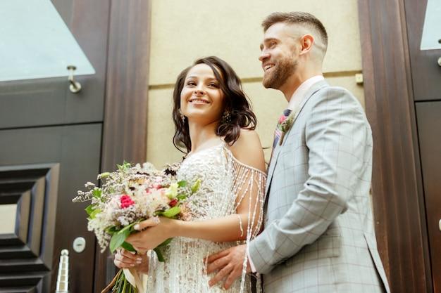 Кавказская романтическая молодая пара празднует свой брак в городе. Бесплатные Фотографии