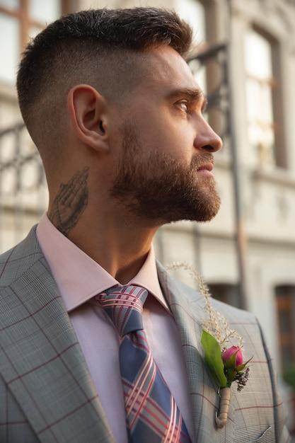 백인 로맨틱 젊은 신랑 도시에서 결혼을 축하. 현대 도시의 거리에 세련된 남자. 가족, 관계, 사랑 개념. 현대 결혼식 무료 사진