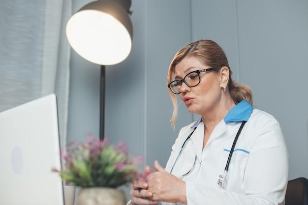 Кавказский старший медик разговаривает онлайн с пациентом, используя ноутбук и в очках, во время разговора на камеру Premium Фотографии