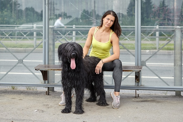 백인 심각한 소녀와 그녀의 검은 털복숭이 브리아 드는 대중 교통 역에 앉아 버스를 기다리고 있습니다. 프리미엄 사진